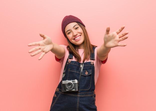 Joven fotógrafo lindo mujer muy feliz dando un abrazo al frente