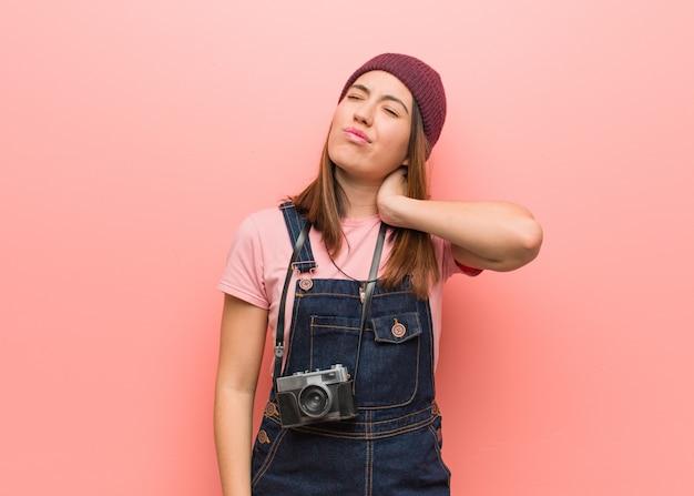 Joven fotógrafo lindo mujer que sufre dolor de cuello