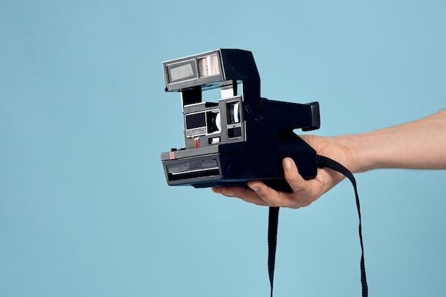 Joven fotógrafo masculino con una vieja cámara en una luz azul emocionalmente posando