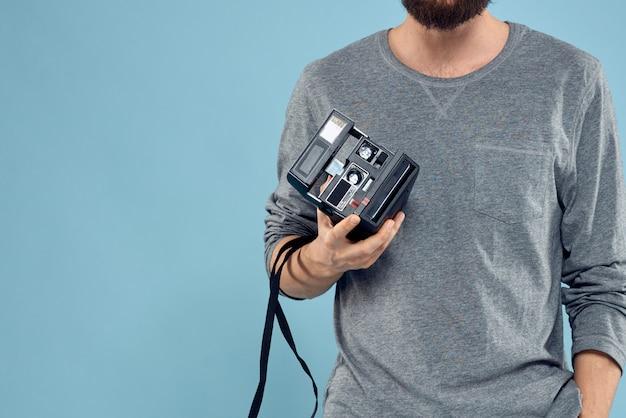 Joven fotógrafo masculino con una vieja cámara en una pared azul claro emocionalmente posando