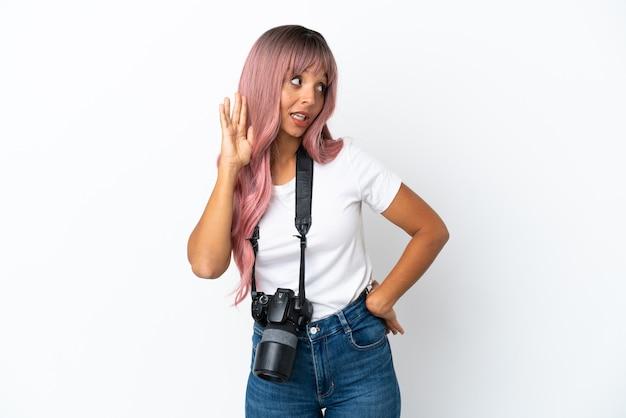Joven fotógrafo mujer de raza mixta con cabello rosado aislado sobre fondo blanco escuchando algo poniendo la mano en la oreja