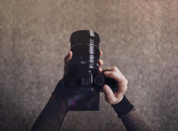 Joven fotógrafo mujer usando la cámara para tomar fotos. tono oscuro, pov o vista superior en ángulo bajo. enfoque selectivo en pantalla lcd