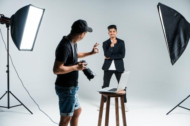 Joven fotógrafo profesional tomando fotos de modelo indio en estudio con leight
