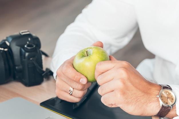 Joven fotógrafo trabajando en una computadora, mesa de trabajo con teclado, cámara, computadora portátil y lentes,