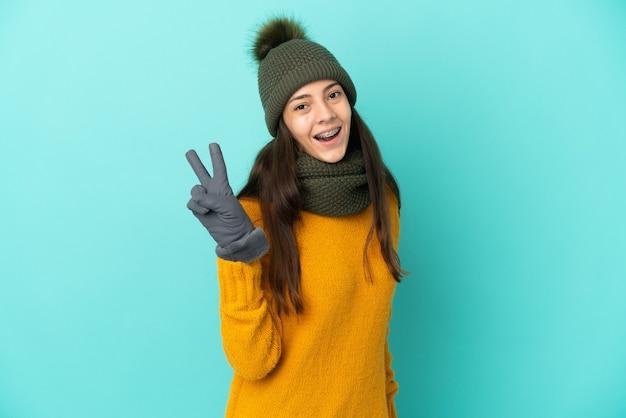 Joven francesa aislada sobre fondo azul con sombrero de invierno sonriendo y mostrando el signo de la victoria