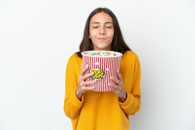 Joven francesa aislada sobre fondo blanco sosteniendo un gran balde de palomitas de maíz