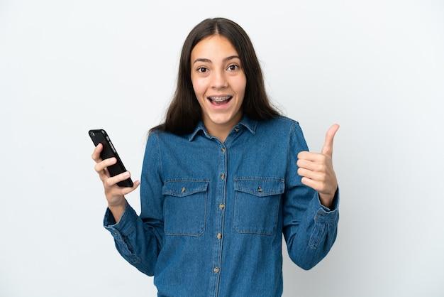 Joven francesa aislada sobre fondo blanco mediante teléfono móvil mientras hace los pulgares para arriba