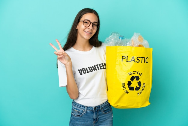 Joven francesa sosteniendo una bolsa llena de botellas de plástico para reciclar sonriendo y mostrando el signo de la victoria