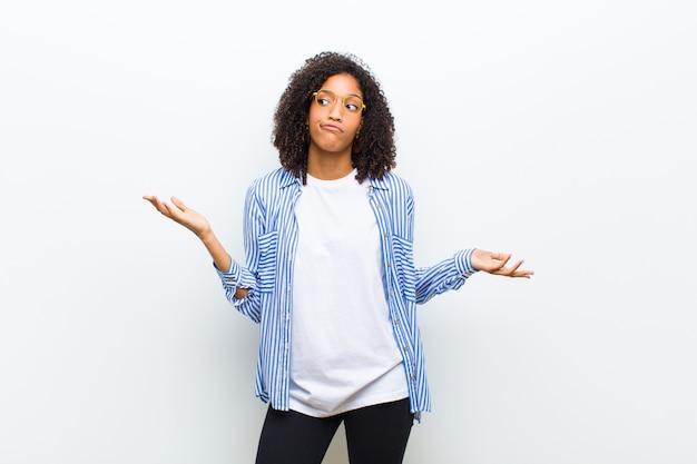 Joven fresca que se siente confundida y confundida, insegura sobre la respuesta o decisión correcta, tratando de tomar una decisión