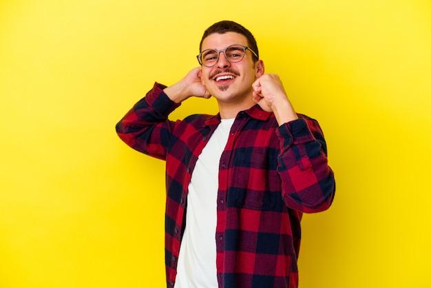 Joven fresco aislado en la pared amarilla celebrando un día especial, salta y levanta los brazos con energía