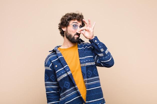 Joven fresco que se siente disgustado, se tapa la nariz para evitar oler un hedor desagradable y desagradable contra la pared