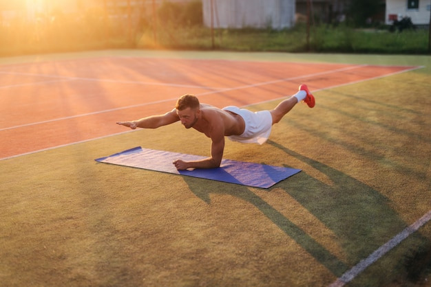 Joven fuerte dedicado hombre haciendo abdominales en el campo de entrenamiento. entrenamiento matutino de principios de verano.