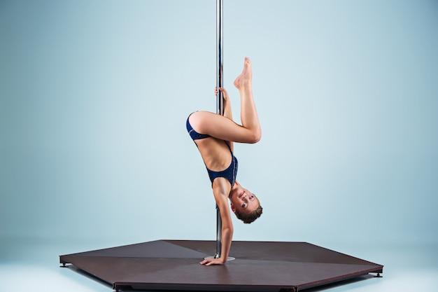 La joven fuerte y elegante que realiza ejercicios acrobáticos en pilón