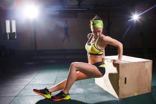 Joven, fuerte y musculosa chica salta en el gimnasio hacia la elevación. entrenamiento de piernas y cardio.