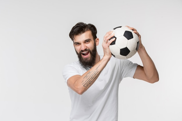 Joven futbolista con balón delante de la pared blanca