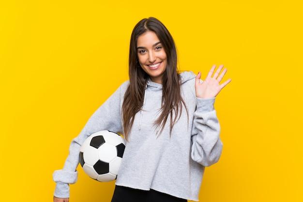 Joven futbolista mujer aislada pared amarilla saludando con la mano con expresión feliz