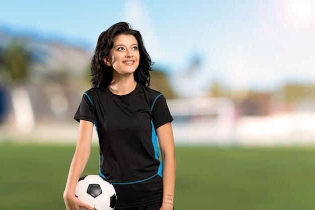 Joven futbolista mujer mirando hacia arriba mientras sonríe al aire libre