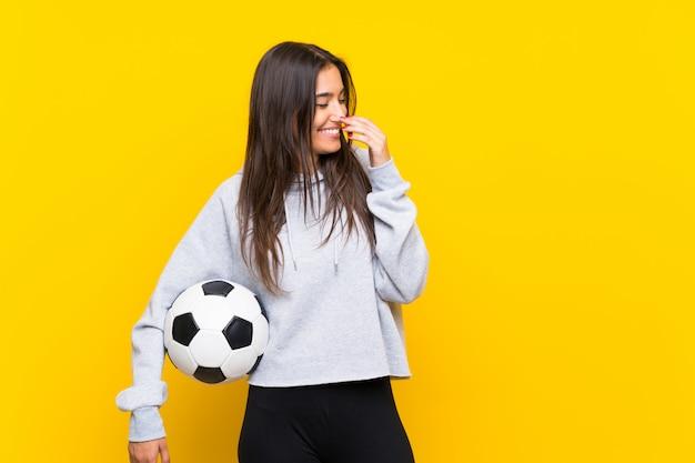 Joven futbolista mujer sobre pared amarilla aislada sonriendo mucho
