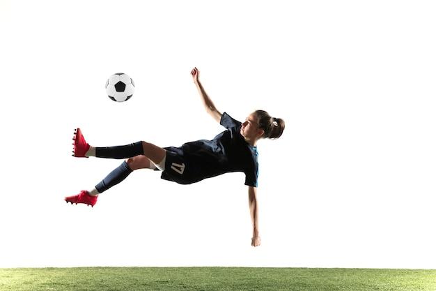 Joven futbolista o futbolista con pelo largo en ropa deportiva y botas pateando la pelota para el gol en salto aislado sobre fondo blanco. concepto de estilo de vida saludable, deporte profesional, afición.