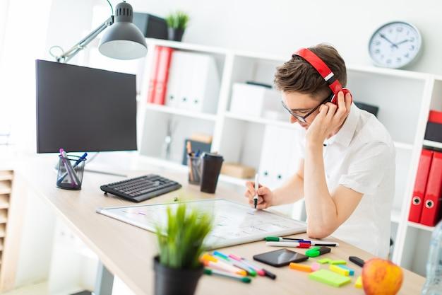 Un joven con gafas y auriculares se encuentra cerca de un escritorio de la computadora. un joven dibuja un marcador en una pizarra magnética.