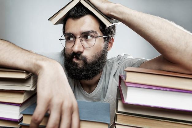 Joven con gafas y una barba se sienta en una mesa con montones de libros. entrenamiento y educación.