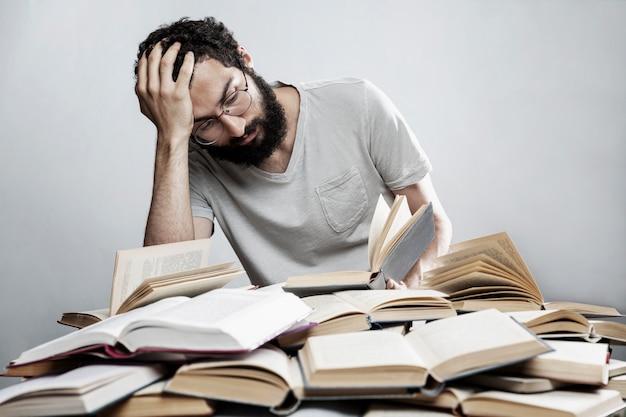 Joven con gafas y barba se sienta en una mesa con una pila de libros abiertos. entrenamiento y educación.
