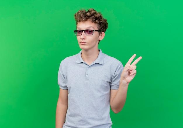 Joven de gafas negras vistiendo polo gris sonriendo mostrando signo v sobre verde