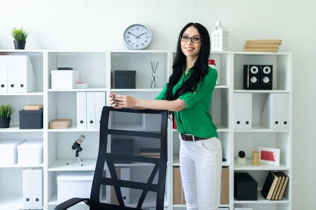 Una joven con gafas se para en la oficina y pone las manos en el respaldo de la silla.