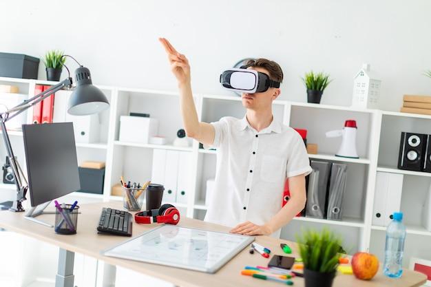 Un joven con gafas de realidad virtual se para cerca de la mesa y levanta el brazo. un joven manosea una página virtual.