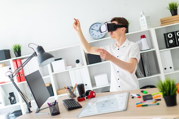 Un joven con gafas de realidad virtual se para cerca de la mesa y levanta el brazo.