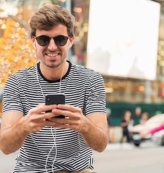 Joven con gafas de sol escribiendo smartphone