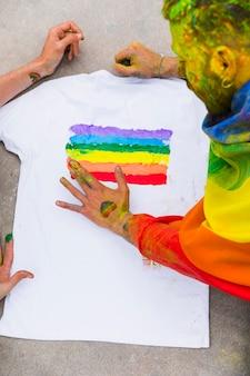 Joven gay dibujo arcoiris en camiseta blanca