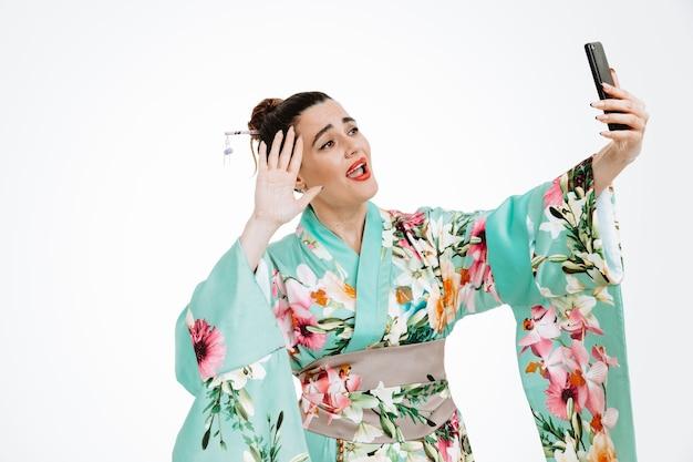 Joven geisha en kimono japonés tradicional sosteniendo un teléfono inteligente con una videollamada feliz y sorprendida sonriendo ampliamente saludando con una mano de pie sobre la pared blanca