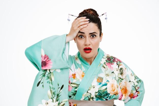 Joven geisha en kimono tradicional japonés mirando al frente confundida y preocupada sosteniendo la mano en la cabeza por error de pie sobre una pared blanca