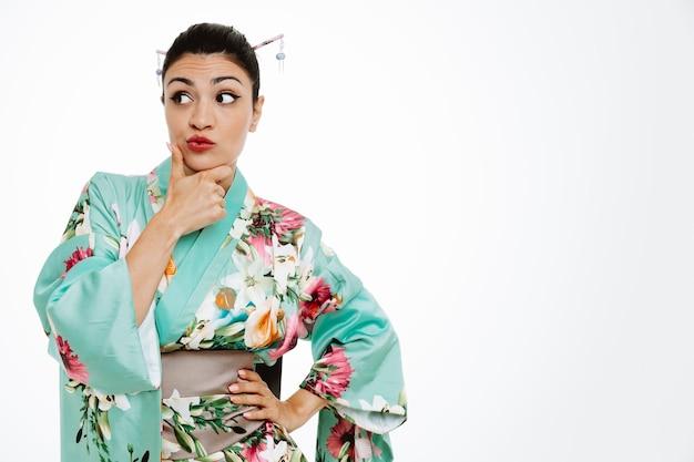 Joven geisha en kimono tradicional japonés mirando a un lado con expresión pensativa con la mano en la barbilla pensando de pie sobre la pared blanca