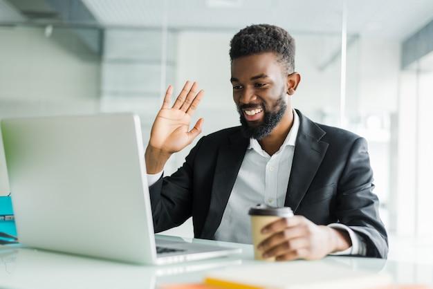 Joven gerente afroamericano con rastrojo sentado frente a la computadora portátil abierta con auriculares mientras tiene una videoconferencia con socios comerciales