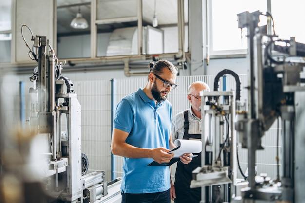 Joven gerente con barba mostrando e inspeccionando el proceso de trabajo del trabajador profesional adulto en la gran fábrica.