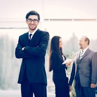 Joven gerente exitoso en el equipo de negocios de fondo en la oficina