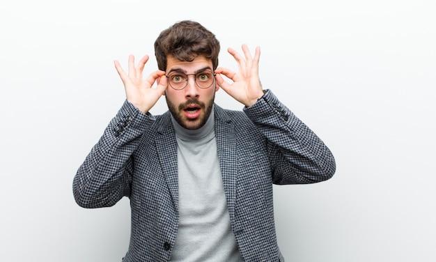 Joven gerente hombre sintiéndose sorprendido, asombrado y sorprendido, sosteniendo gafas con una mirada asombrada e incrédula contra la pared blanca