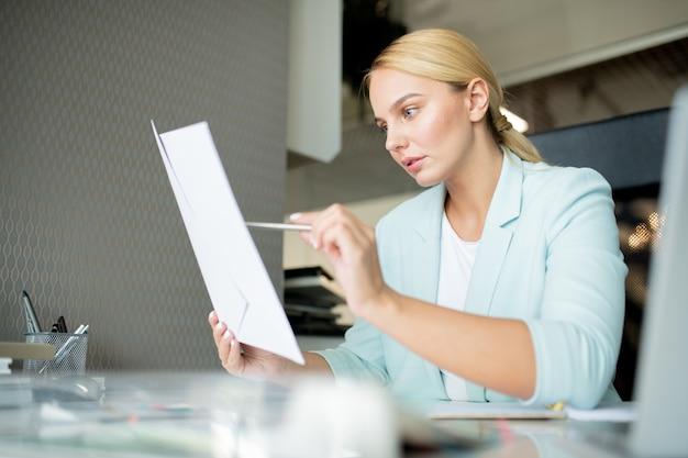 Joven gerente o banquero apuntando al documento financiero mientras lo lee o verifica datos por lugar de trabajo