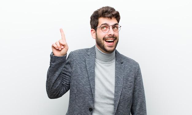 Joven gerente que se siente como un genio feliz y emocionado después de darse cuenta de una idea, levantando alegremente el dedo, ¡eureka! contra la pared blanca
