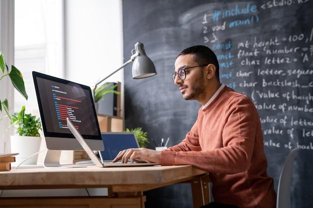 Joven gerente de ti informal sentado frente a una computadora portátil en la oficina y analizando información codificada