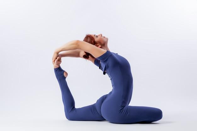 Joven gimnasta atlética en mono gimnástico hace estiramientos en pose difícil