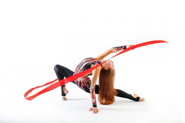 Joven gimnasta con cinta roja sobre fondo blanco.
