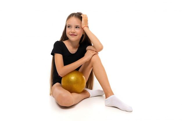 Joven gimnasta niño en un traje de baño deportivo negro se sienta con una pelota sobre un fondo blanco.