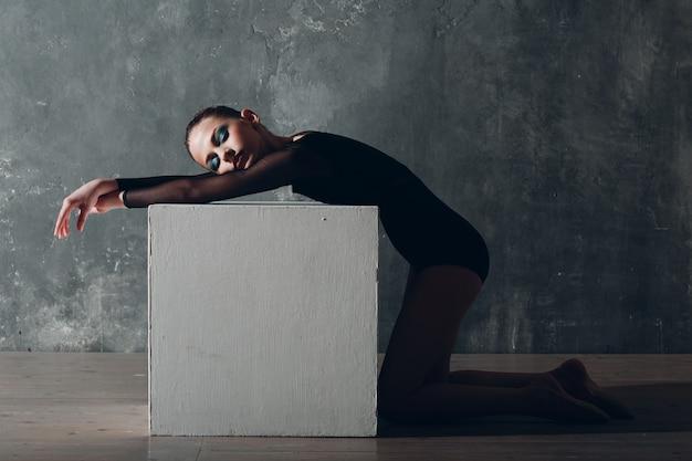 Joven gimnasta profesional mujer gimnasia rítmica relajante con cubo blanco en el estudio.