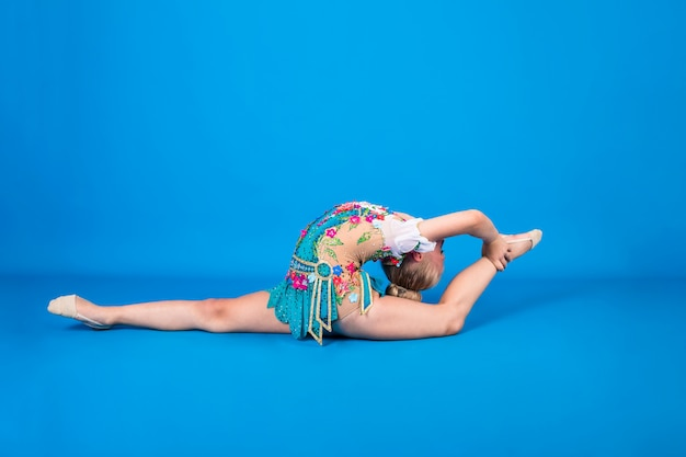 Una joven gimnasta realiza un ejercicio con una desviación en la espalda sobre una pared azul aislada