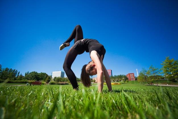Joven gimnasta sobre césped en día soleado
