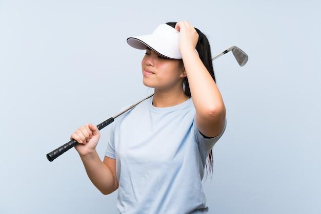 Joven golfista asiática que tiene dudas y con expresión de la cara confusa