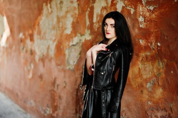 Joven gótica en falda de cuero negro y chaqueta contra la pared del grunge.